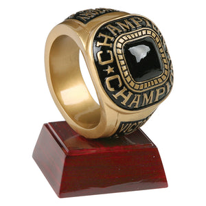 "Champion trophy featuring a square shaped maroon glossy base with a large gold and black ring sitting on top vertically. The ring has a black faux stone and says ""CHAMPION"" around the center."