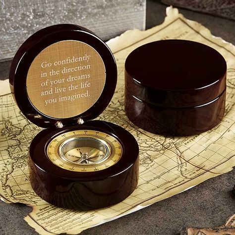High gloss rosewood round hinged box with compass inside. Compass features a lid that opens up to display a gold plate engraved with a special message on top. The bottom half of the compass is a golden compass that matches the gold engraved plate.