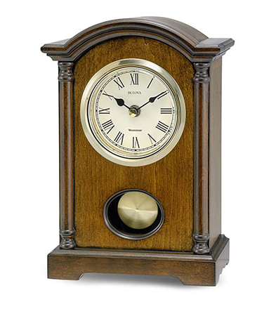 Rectangle shaped walnut clock with pendulem and curved top. Features a white face with black roman numerals. Clock face is outlined in gold.