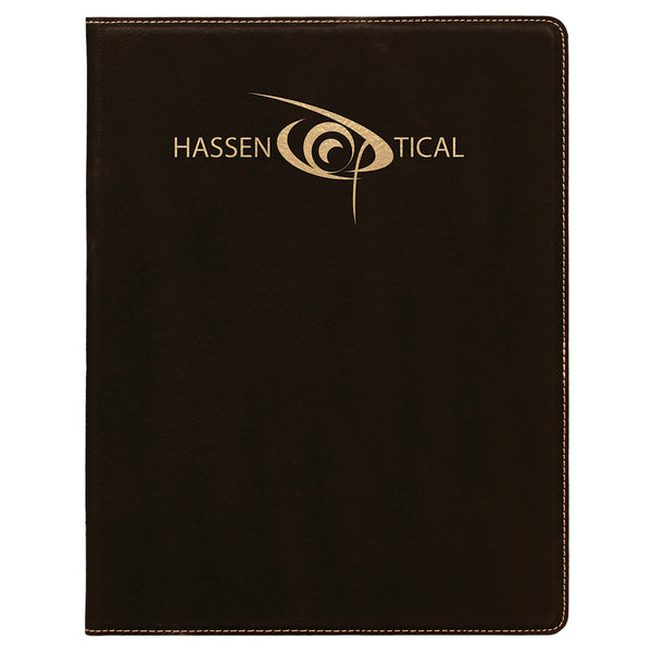 Small black leatherette portfolio. The front of the portfolio is engraved with a gold company logo at the top center. The portfolio opens up to reveal a lined white note pad.