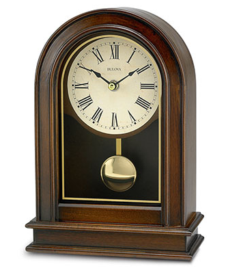 Walnut colored wooden rectangluar bottom clock with curved top featuring a shiny gold pendulum, glass cover, and a cream colored face with black roman numerals.