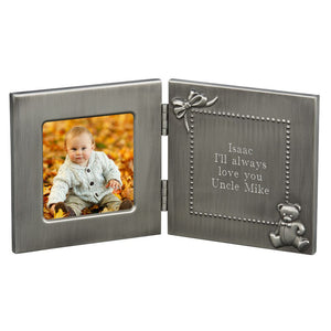 Brushed silver hinged baby frame that opens up to reveal a photo frame on the left side, and a square engraving space on the right side. The engraving space is outlined in small dots, a bow in the upper left corner, and a teddy bear in the bottom right corner.