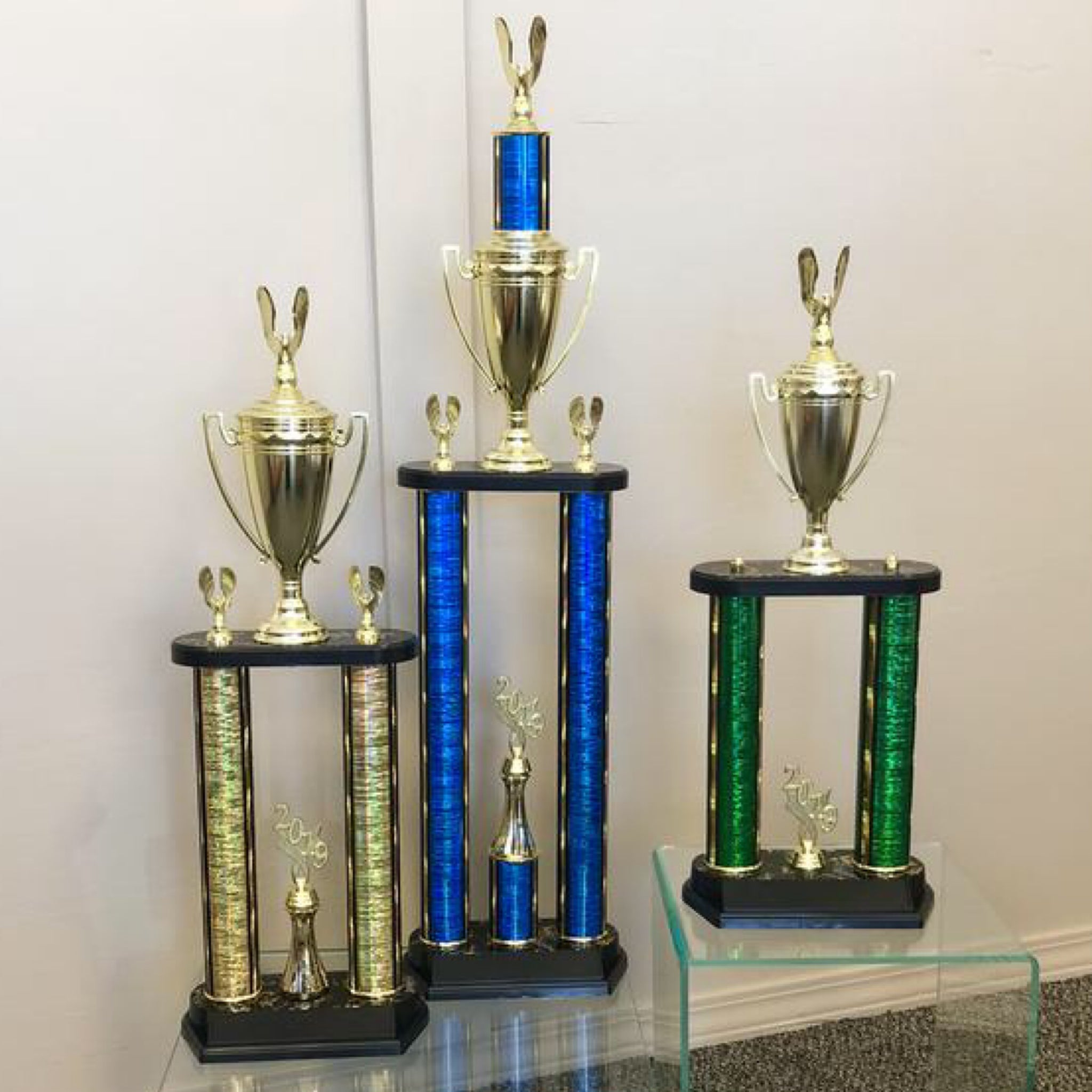Medium size two post column trophies. Gold two post trophy with cup. Blue two post column trophy with cup. Green two post column trophy with cup.