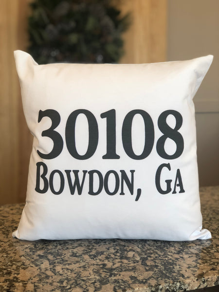 "White square pillow featuring large black writing. The zip code ""30108"" is engraved on one line followed by ""Bowdon, GA"" beneath it."