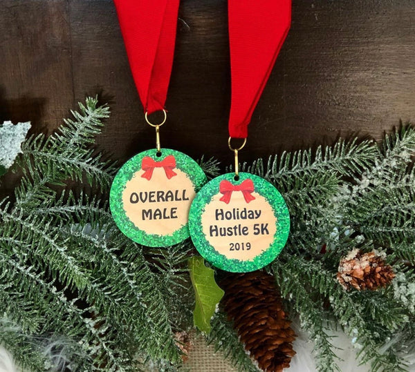 Wood medallions printed with a colorful red and green wreath attached to a red neck ribbon.