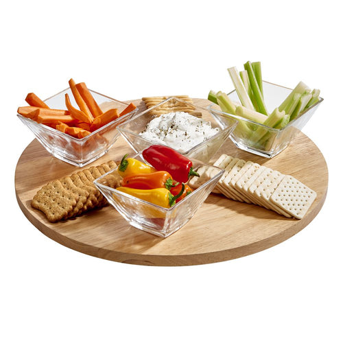 Large round lazy susan cutting board displaying crackers, carrots, celery, and dip.