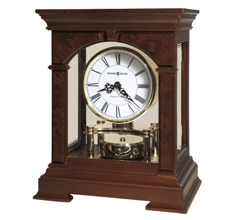 Large mantel clock, finished in Cherry bordeaux design on top, bottom, and four columns at each corner. Features decorative olive ash burl finished overlays on the front and gold detail on the side glass panels.  A revolving, polished brass-finished pendulum sits below the dial. The clock has a white face with black hands and roman numerals.