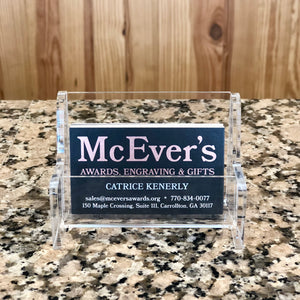 Clear acrylic bench shaped business card holder for table top. Holding a stack of black business cards.