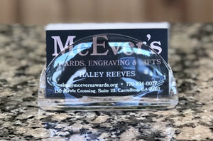 Clear acrylic semi circle shaped business card holder for table top. Holding a stack of black business cards.