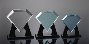 Left: Large clear diamond shaped acrylic award sitting on a black base. Center: Medium jade colored diamond shaped acrylic award on black base. Right: Small blue diamond shaped acrylic award on a black base.