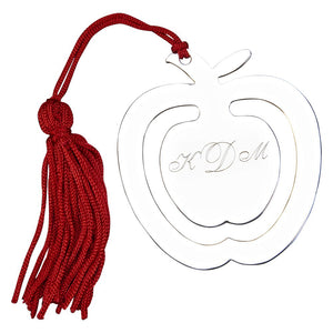 Monogrammed shiny silver apple shaped bookmark with a red tassel.