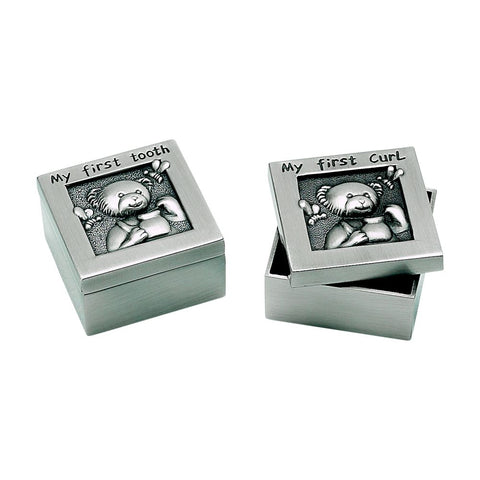"Two small square silver boxes with lids that feature a teddy bear. On the lid of each box reads ""My First Tooth"" or ""My First Curl"" in black letters. A name is engraved on the side of each of the boxes."
