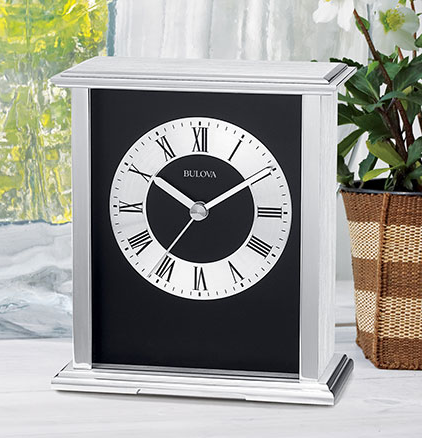 Silver metal Bulova clock featuring a rectangular construction, black inside, and a silver face with black roman numerals.