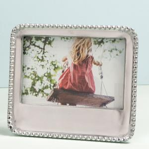 Shiny silver metal picture frame with round beaded edges. Corners are rounded. There is a space at the bottom for an engraved message. Holds a 4