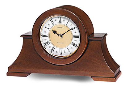 Large walnut colored wooden mantel clock with a white and gold face featuring black roman numerals.