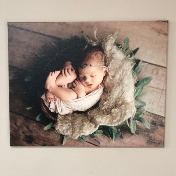 Custom photo canvas print of a newborn baby wrapped up in a floral basket.