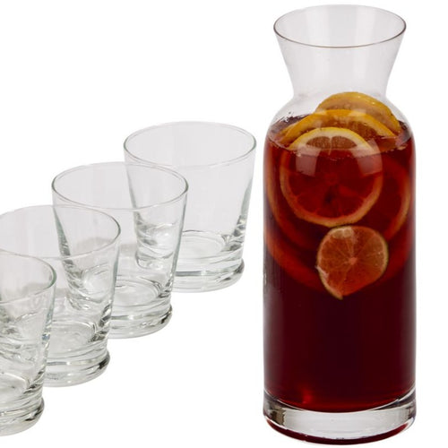 Four short engraved glasses and a tall glass carafe holding sangria.