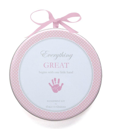Round pink and white metal tin that contains a baby girl clay hand print kit.