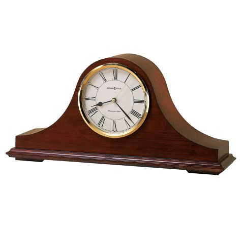 Large cherry colored wood mantel clock featuring a white face with black roman numerals outlined in shiny gold.