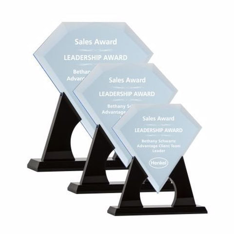 Small, medium and large diamond shaped clear engraved acrylic awards sitting on black acrylic stands.