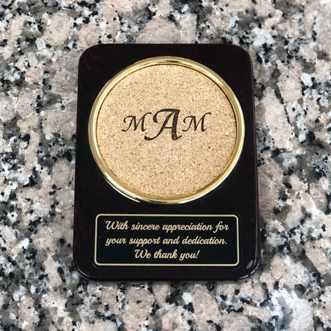 High gloss rosewood rectangular shaped coaster with round cork area to sit your drink. Cork is engraved with a  monogram. below the round cork coaster is a black and gold engraved plate with a special message.