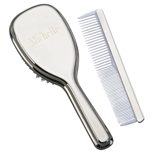 Engraved shiny silver baby brush with handle and baby comb with white teeth.