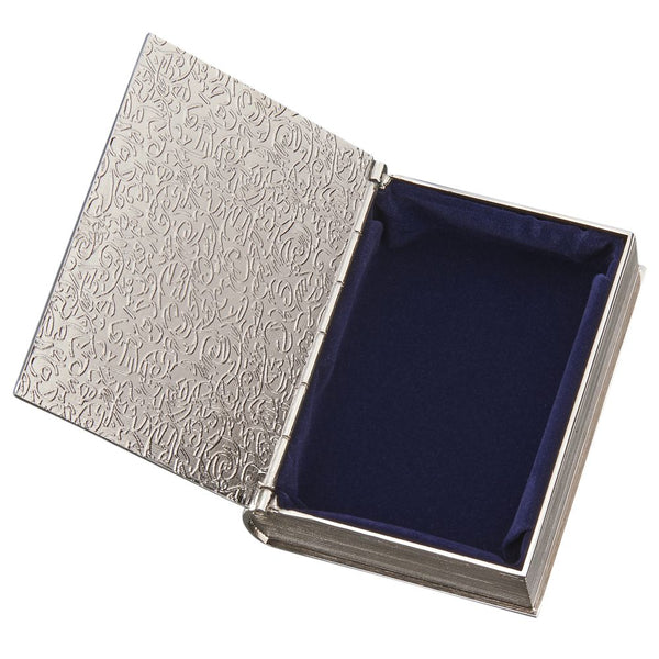 Small silver book shaped keepsake box with a hinged cover. The front of the box features a border, a cross, and a name engraved at the bottom.The edges are designed to look like the spine and pages of a book. The inside is lined in navy blue velvet material.