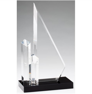 Large tower sculpture crystal award featuring two free standing skinny towers on the left hand side of the award. They are diamond shaped and have slanted tops. The largest part of the award is  beveled triangle shaped crystal that can be engraved. All are attached to a rectangle shaped black glass base.