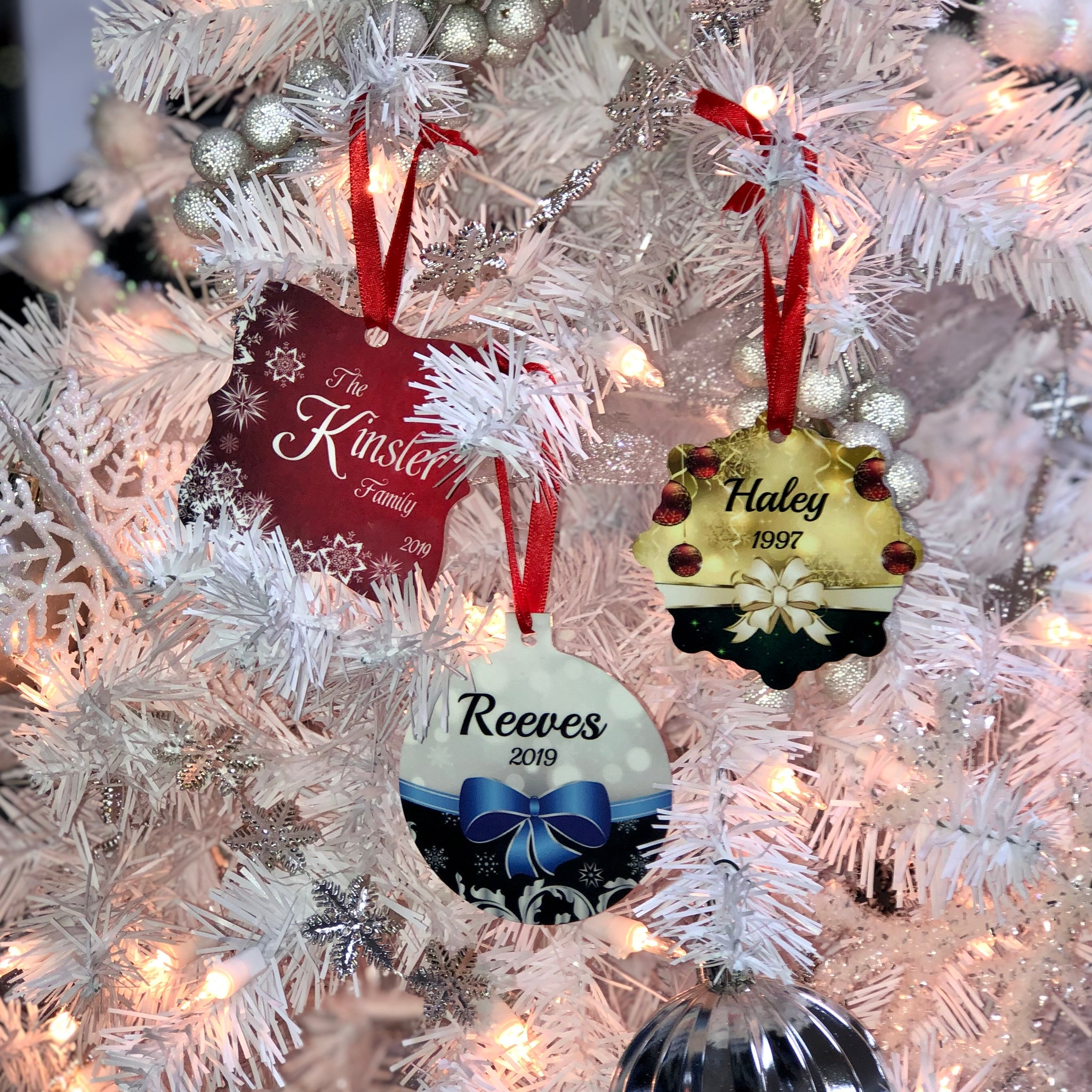White Christmas tree holding different shaped ornaments with different colors and designs on each.