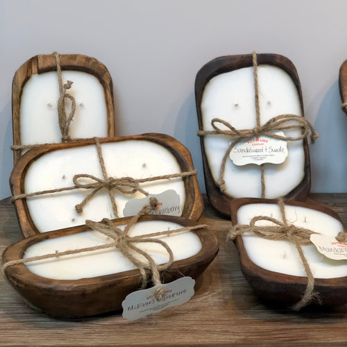 Hand poured white was candles in large brown wood dough bowl containers.