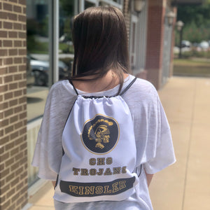 A white drawstring bag engaved with a school logo, school name, and last name on the back of a girl with a white shirt on.