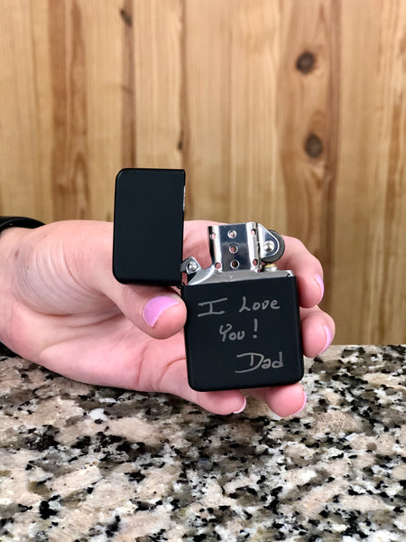 Matte black lighter engraved with custom handwriting on the bottom half.
