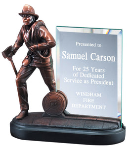 Firefighter service award featuring an oval shaped black base, a bronze firefighter carrying an ax and a water hose, and a thin rectangle piece of glass that can be engraved with award details.