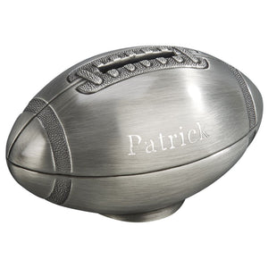 Brushed silver football shaped coin bank with a slot for coins on the top where the laces are. The side of the piggy bank is engraved with a boy's name.