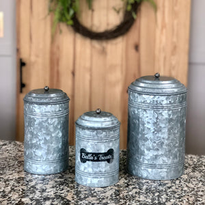 Set of three galvanized treat canisters engraved with a black bone and dog's name in a silver cursive font. Canisters are round and have a lid with a ball handle in the center.