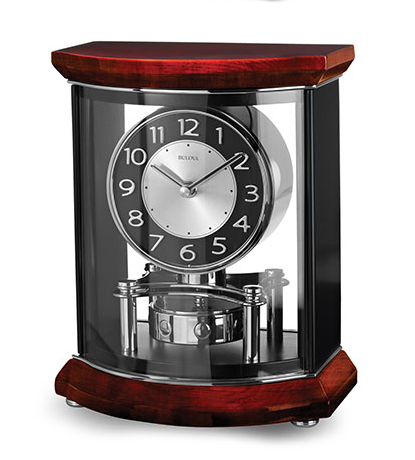 Large clock featuring a solid hardwood top and base, high-gloss piano finish over mahogany stain with a clear acrylic front and back. Sides are matte black. Polished chrome inlaid accents, bun feet and revolving pendulum. Black and silver clock face.