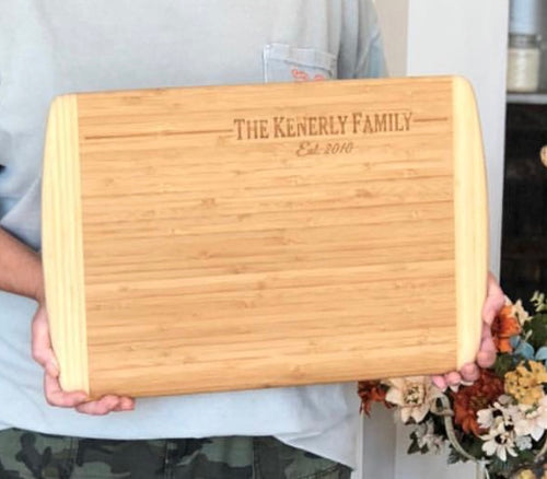 Two tone rectangle wood cutting board featuring two curved ends that are a lighter wood color than the center. The top right is engraved with a family name and date.