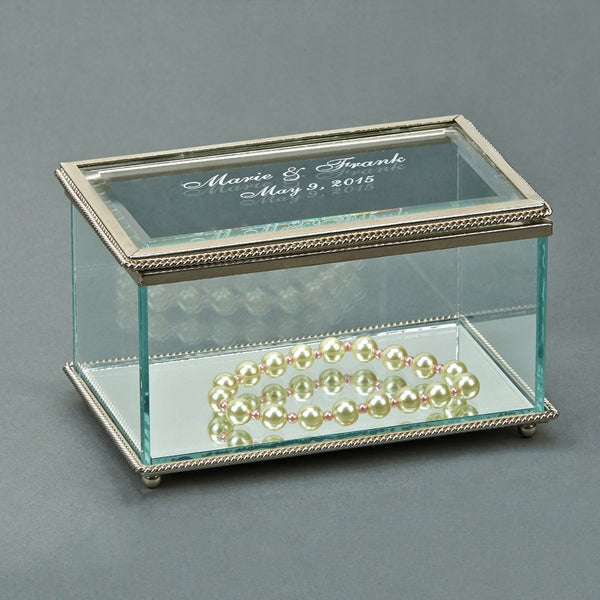 Rectangle shaped glass jewelry box with a silver braided edge. The top is engraved with with names and a wedding date in a frosty white color. The bottom of the jewelry box is a glass mirror.