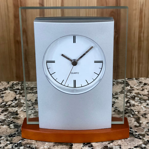 Silver and glass clock with light wood base featuring a white face with silver hands.
