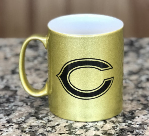 "Gold sparkle glass coffee mug engraved with a black ""C"" logo for a school."