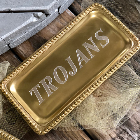 "Rectangle shaped shiny gold tray with a beaded edge. The shiny gold tray is engraved to read ""TROJANS"" in the center."