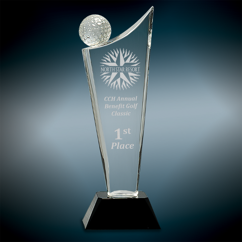 Tall engraved crystal award featuring a square tapered black glass base and a sail shaped crystal. On the left side of the top of the crystal sits textured golf ball.