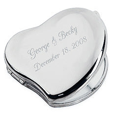 Heart shaped silver compact mirror. The front is engraved with two names and a wedding date in a cursive font.