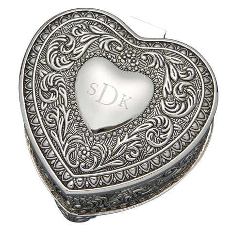 Heart shaped hinged jewelry box with an ornate paisley and floral design on the top and sides. Top features small flat heart shape in center that is engraved with a monogram.