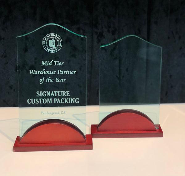 Small and large jade colored engraved standing acrylic awards with a cherry wood colored base.