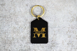 "Rectangle shaped black brass keychain with peaked top and shiny gold key ring. The keychain is engraved with a large ""M"" and a last name going through the center of it. Engraving is brass colored."