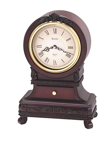 Large Bulova Knollwood clock featuring four feet, an ornate design on the bottom half of the clock, and a large round cream colored clock face with black hands and roman numerals.