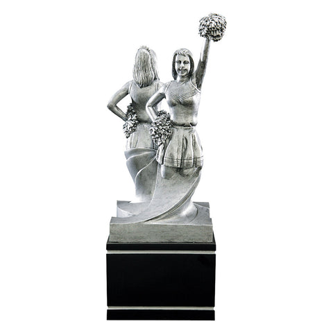 Large black and silver cheerleading trophy featuring a black square wood base and two cheerleaders back to back perfoming different cheerleading tasks. One cheerleader has one hand on her hip and the other raised above her had with a pom pom. The opposite side displays a cheerleader with both hands on her hips.