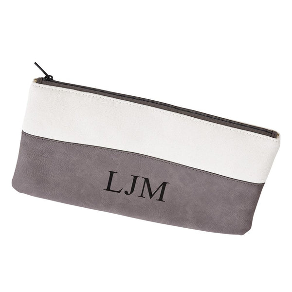 Engraved cosmetic bag featuring a rectangle shape and zipper. The bottom half is grey leatherette material and is monogrammed. The Top half is white canvas colored.