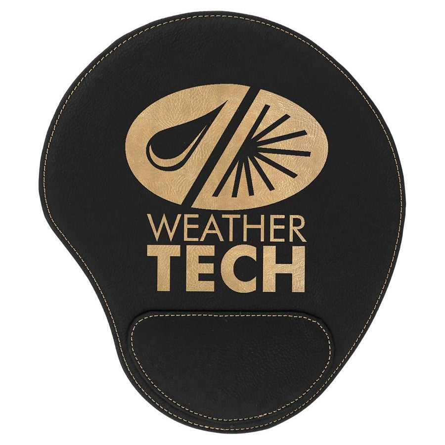Black leatherette mouse pad with a pad at the bottom to rest your wrist. The mouse pad is engraved with a large gold company logo.